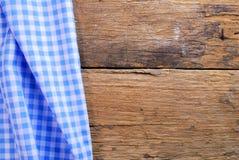 由方格的餐巾做的背景在老木桌 免版税库存图片