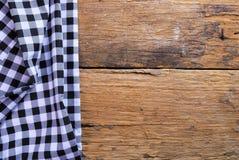 由方格的餐巾做的背景在老木桌 免版税库存照片