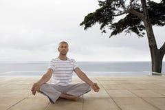 由无限水池的人实践的瑜伽 免版税库存图片