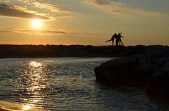 由日出的妇女的剪影海上 免版税图库摄影