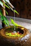 由日本茶屋子的一石水盆chozubachi,当在&五颜六色的槭树叶子下落的一片竹管子供应的水 免版税库存图片