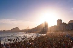 由日落的拥挤科帕卡巴纳海滩在里约热内卢,巴西 免版税库存照片