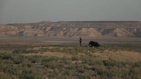 由日落50p的人立场近的野营的帐篷 股票录像