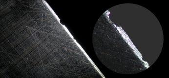 由显微镜的剃须刀 微观被抓的钢表面 免版税库存照片
