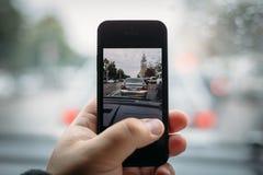 由智能手机在手中供以人员射击城市交通从他的汽车,被定调子 库存照片