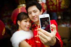 由智能手机的可爱的夫妇selfie照片有红色纸汉语的 免版税库存图片