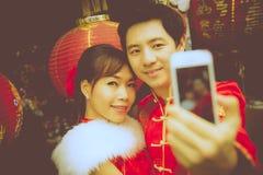 由智能手机的可爱的夫妇selfie照片有红色纸汉语的 免版税库存照片
