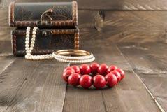 由木头做的圆的红色小珠在颜色木背景 免版税库存图片