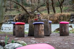 由树日志和椅子做的表,与五颜六色的坐垫在每把日志/椅子,在河附近 野餐的概念,吃户外 库存照片