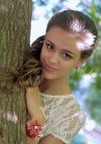 由树的俏丽的女孩 图库摄影