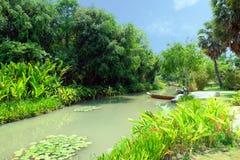 由树围拢的运河的小船在夏天 库存图片