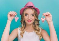 由桃红色布料被做的可爱的女孩拿着两手工制造心脏 她看对与a的照相机 库存照片