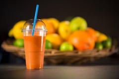 由桔子新鲜的圆滑的人做的杯,红萝卜 免版税图库摄影