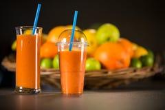 由桔子新鲜的圆滑的人做的杯,红萝卜 免版税库存照片