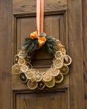 由橙色垂悬做的圣诞节装饰花圈在门 免版税库存图片