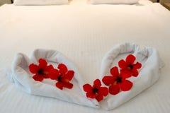 由毛巾做的心脏在蜜月床 图库摄影