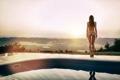 由水池的性感的妇女在日落期间 免版税库存图片