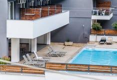 由水池的轻便折叠躺椅在一家地方旅馆 图库摄影