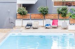 由水池的轻便折叠躺椅在一家地方旅馆 免版税库存图片