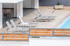 由水池的轻便折叠躺椅在一家地方旅馆 库存照片