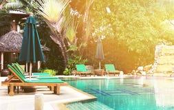 由水池的轻便马车休息室在温暖的太阳的旅馆发出光线 库存照片