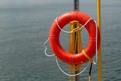 由水的橙色救生圈和绳索 免版税库存照片