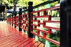 由池塘的木细长立柱,与中国古典设计的木扶手栏杆 免版税库存照片