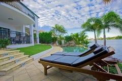 由池的轻便折叠躺椅在江边豪宅 免版税库存照片
