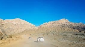 由汽车和冒险旅行通过尘土到山 图库摄影