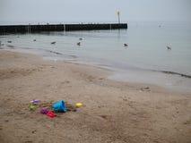 由沙子决定的疏散五颜六色的玩具在海的海滩,没人 免版税库存图片