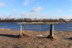 由河的一条空的长凳 库存图片