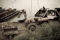 由河的老拖拉机和小船 免版税库存照片