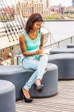 由河的非裔美国人的妇女阅读书在纽约 库存照片