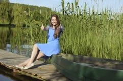 由河的年轻人微笑的俏丽的女孩有她的 免版税库存照片