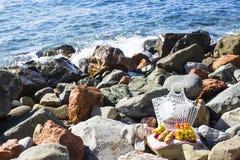 由海休息用葡萄、苹果、梨、长方形宝石、酒和一个篮子在床罩 库存图片