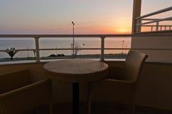 由海制表和在阳台的两把椅子在日出 库存图片