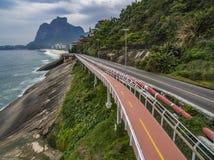由海和自行车道路的高速公路 在海旁边的柏油路 汽车广告背景 免版税图库摄影