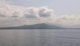 由海洋的山在云彩下 图库摄影