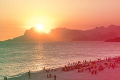 由海洋的橙色日落在Piratininga, Niteri,当太阳浸洗behing Gavea石头在里约热内卢 充分海滩peop 库存图片
