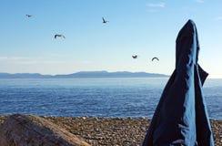 由海洋的蓝色防风雨夹克 图库摄影