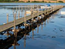 由海洋自然风景背景的老木码头跳船 图库摄影