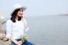 由海滩海洋湖河的自由粗心大意的causual秀丽享用放松在夏天春天公园微笑的时间在她的面孔举行花 免版税库存照片