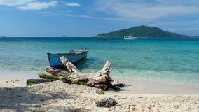 由海滩的一老渔船在一块清楚的蓝色绿松石 免版税库存照片