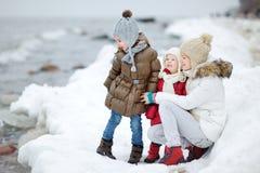 由海照顾和她的女儿在冬天 免版税库存照片