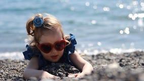 由海的一个儿童游戏Pebble海滩的在与玻璃的一个有风晴天以心脏的形式 股票视频