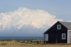由海的一点房子有大白色云彩的 免版税库存图片