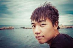 由海的亚洲男孩画象 免版税图库摄影
