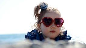由海的儿童女孩海滩的在与玻璃的一个有风晴天以心脏的形式 爱的概念和 影视素材