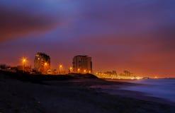 由海的城市在晚上 图库摄影