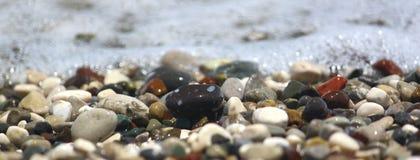 由海的小卵石海滩的,横幅和纹理的 焦点奔跑通过中部 免版税库存照片